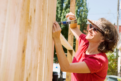 Smiling woman building fence
